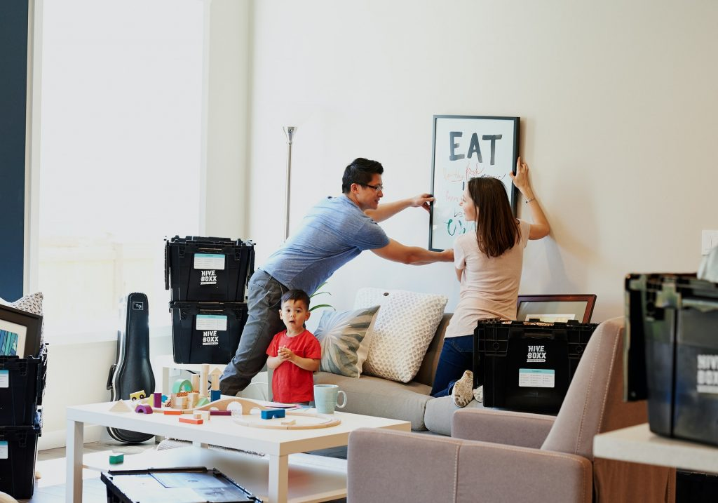 Family moving into a new home hanging a picture